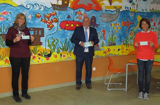 Geschäftsstellenleiter Ernst Janak überreicht den Lehrerinnen Annette Brandl (l.) und Astrid Löw die Masken für die Grundschüler in Tettenweis